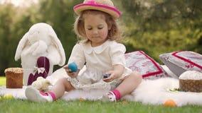 L'enfant heureux s'assied sur un pré autour de la décoration de Pâques