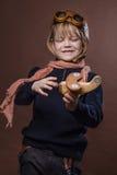 L'enfant heureux s'est habillé en chapeau et verres pilotes Enfant jouant avec l'avion en bois de jouet Rêve et concept de libert photos libres de droits