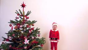 L'enfant heureux s'est habillé en Santa Claus sautant près de l'arbre de Noël, attendant des présents banque de vidéos