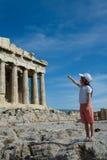 L'enfant indique la façade antique de parthenon dans Acrop photo libre de droits