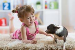 L'enfant jouant avec le chien se trouvant sur le plancher à la maison Photographie stock