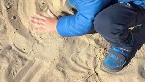 L'enfant jouant avec le sable, se ferment tiré de ses petites mains banque de vidéos
