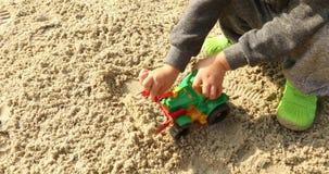 L'enfant jouant le raod travaille avec l'excavatorin de jouet en sable banque de vidéos