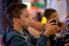 L'enfant joue avec émotion sur des machines de jeu dans le divertissement image stock