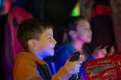 L'enfant joue avec émotion sur des machines de jeu dans le divertissement image libre de droits