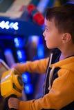 L'enfant joue avec émotion sur des machines de jeu dans le divertissement photo stock