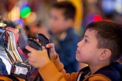 L'enfant joue avec émotion sur des machines de jeu dans le divertissement photos libres de droits