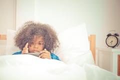 L'enfant joue avec le téléphone portable sur le lit avec le réveil Photo libre de droits