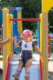 L'enfant joue sur le terrain de jeu Photographie stock libre de droits