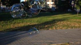 L'enfant laisse de grandes bulles en parc de ville Plan rapproché Mouvement lent banque de vidéos