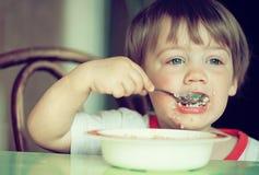 L'enfant lui-même mange de la céréale Photographie stock libre de droits