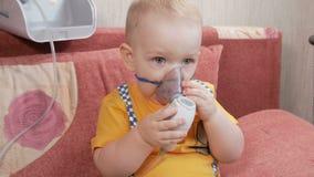 L'enfant lui-même tenant un masque d'un inhalateur et respire la médecine à la maison Traite l'inflammation des voies aériennes p banque de vidéos