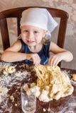 L'enfant malaxent la pâte dans un foulard Images stock