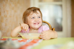 L'enfant mange avec la cuillère Photos libres de droits
