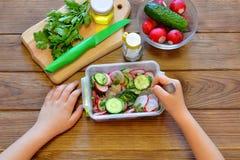 L'enfant mange d'une salade avec le radis et les concombres Ensemble de produits pour faire cuire la salade végétale sur le fond  photos stock