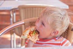 L'enfant mange de la pizza en café, photo teintée photo stock