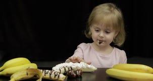 L'enfant mange la banane, la fraise avec du chocolat fondu et la cr?me fouett?e banque de vidéos