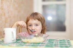 L'enfant mange la pomme de terre avec la cuillère Image libre de droits
