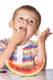 L'enfant mange une pastèque Photo stock