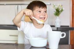 L'enfant masculin heureux dans le T-shirt occasionnel mange du gruau délicieux, boit de la compote, a la consommation saine, se r images stock