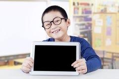 L'enfant masculin tient l'écran vide de comprimé Image libre de droits
