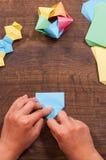 L'enfant met les modules créativité du ` s d'enfants faite de papier, métiers d'origami, artisanat pour des enfants handmade Sur  photographie stock libre de droits