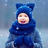 L'enfant mignon, garçon en hiver vêtx jouer sous la neige photo libre de droits