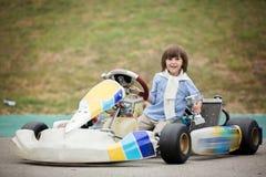 L'enfant mignon, montant vont chariot, gagne la tasse de champion photos libres de droits