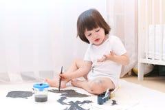 L'enfant mignon regarde les mains sales barbouillant avec la gouache Photographie stock