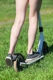 L'enfant monte la poussée-bicyclette sur l'herbe verte, vue arrière en gros plan aux jambes portant des chaussures Photo stock