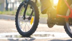 L'enfant monte un plan rapproché de bicyclette passant par un magma et éclaboussant l'eau dans les rayons du coucher de soleil pe photos stock