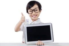L'enfant montre le comprimé et le pouce dans le studio Photo stock