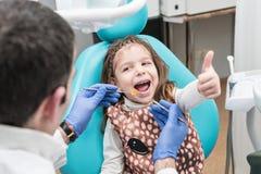 L'enfant montre le pouce au dentiste photographie stock libre de droits