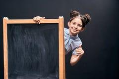 L'enfant montre un signe de l'approbation se tenant au conseil pédagogique écolière positive jetant un coup d'oeil par derrière u photos libres de droits