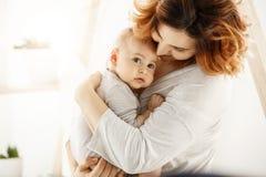 L'enfant nouveau-né mignon regarde frightenedly de côté tandis que jeune bébé beau de huggs de mère doucement exprimant son amour Photo stock