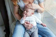 L'enfant nouveau-né rit dans les bras de sa mère Image stock