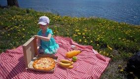 L'enfant ouvre la bo?te en carton avec la pizza sur le littoral banque de vidéos