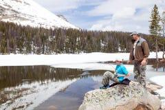 L'enfant a pêché un poisson dans un lac de montagne Père prêt à aider Image stock