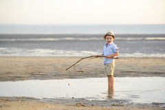 L'enfant pêche sur la plage au bord de la mer Image stock
