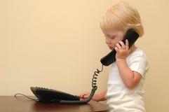 l'enfant parle le téléphone Image libre de droits
