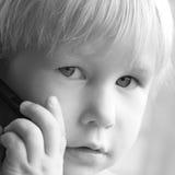 L'enfant parle par le téléphone photographie stock libre de droits