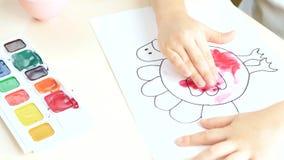 L'enfant peint avec des aquarelles au-dessus de papier utilisant un doigt clips vidéos