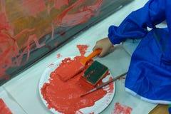 L'enfant peint le mur en plastique avec la couleur rouge Images stock