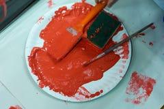 L'enfant peint le mur en plastique avec la couleur rouge Photographie stock libre de droits