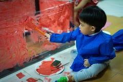 L'enfant peint le mur en plastique avec la couleur rouge Image libre de droits