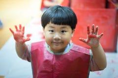 L'enfant peint le mur en plastique avec la couleur rouge Image stock