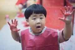 L'enfant peint le mur en plastique avec la couleur rouge Photographie stock
