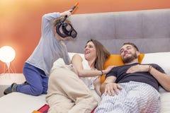 L'enfant plaisante avec des parents sur le lit pendant le matin Image stock