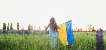 L'enfant porte le flottement drapeau bleu et jaune de l'Ukraine images stock