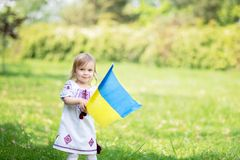 L'enfant porte le flottement drapeau bleu et jaune de l'Ukraine dans le domaine Jour de la D?claration d'Ind?pendance du ` s de l photos stock